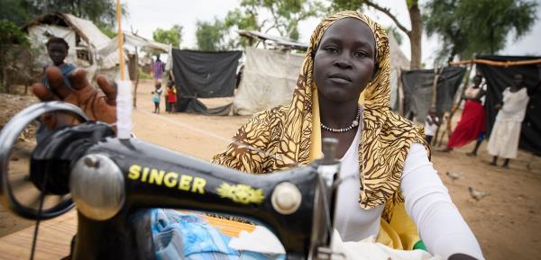 Hawa har ställt ut symaskinen utanför sitt hem. Då blir det lättare att ta upp beställningar på skoluniformer. Pengarna hon får in är ett välkommet tillskott till familjen med sex barn.