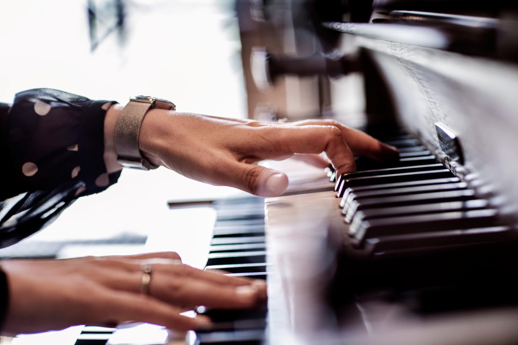 En person som spelar på en orgel. Bara händerna och orgeltangenterna syns.