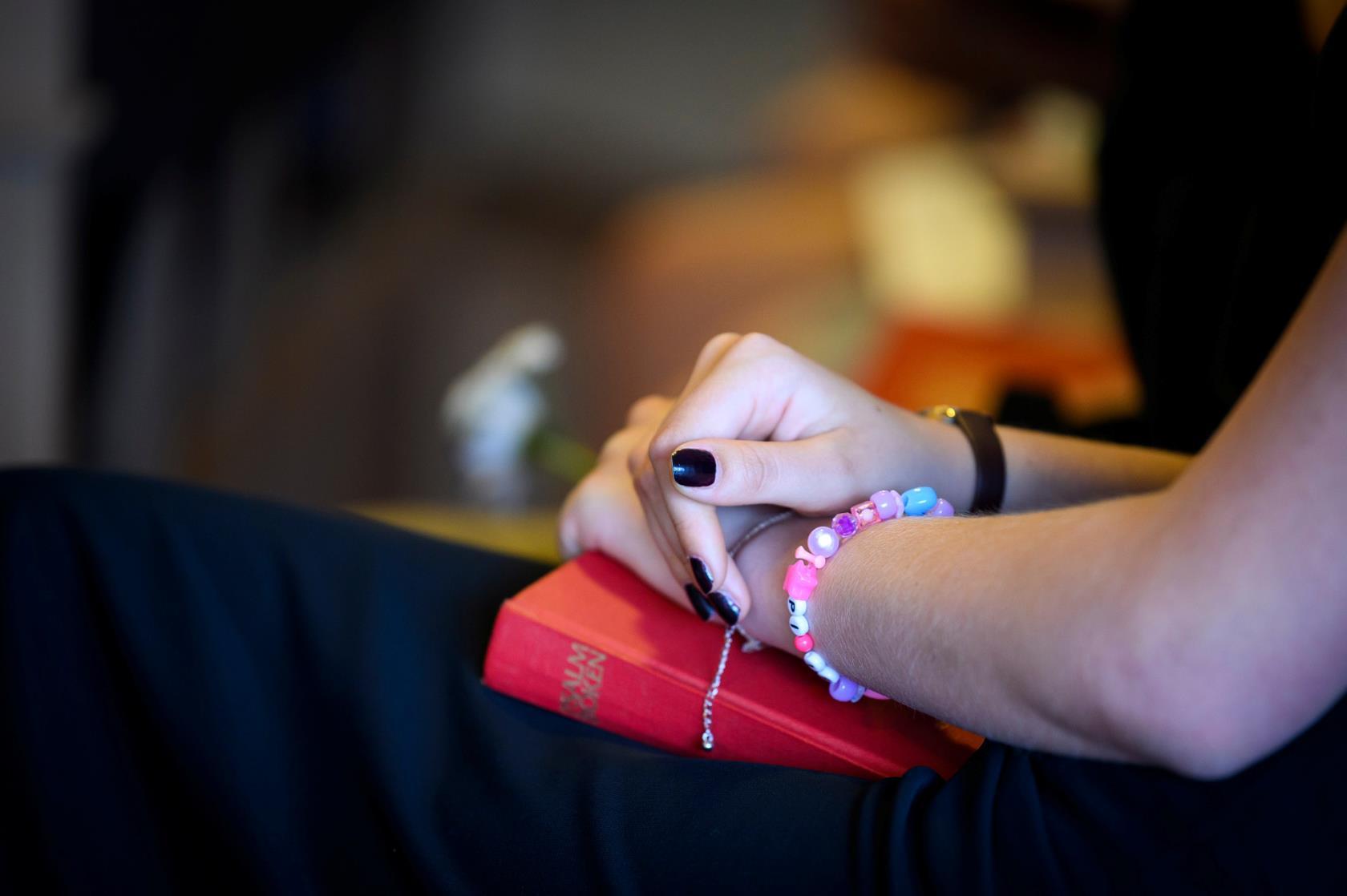 Händer som håller i en psalmbok