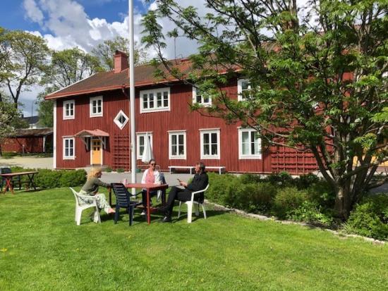 Tre personer sitter i sommargrönska framför den röda Församlingsgården.