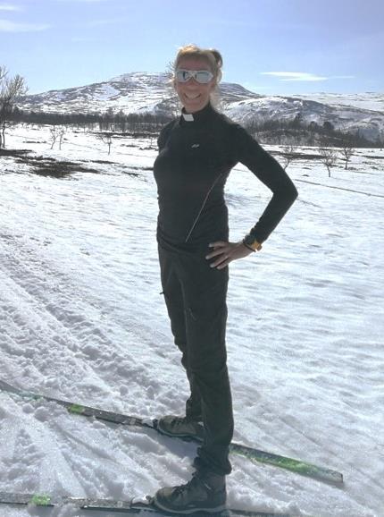 Fjällpräst på skidor i strålande sol.